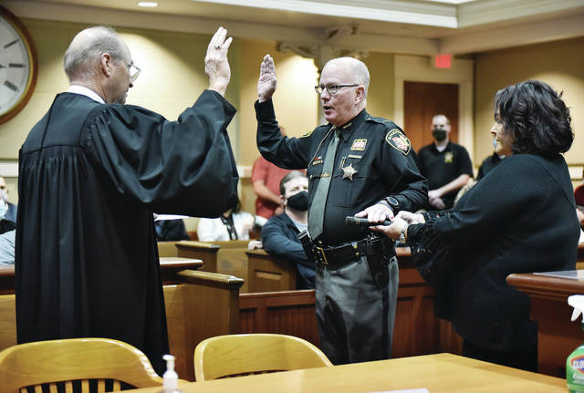 Jim Frye, center, is sworn in as the new Shelby County sheriff by Judge Bill Zimmerman as Frye's wife, Lori Frye holds a Bible in the Shelby County Municipal Courtroom on Monday, Dec. 28.