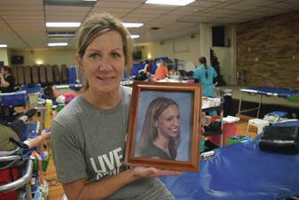 Susan Leugers holds a photo of her daughter, Chelsea Lukey, at the 2020 memorial blood drive.
