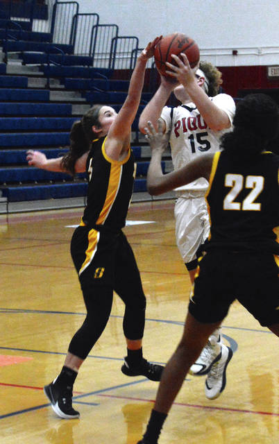 Sidney sophomore guard Lexee Brewer blocks a shot by Piqua's Karley Johns during a Miami Valley League game on Monday at Garbry Gymnasium in Piqua.