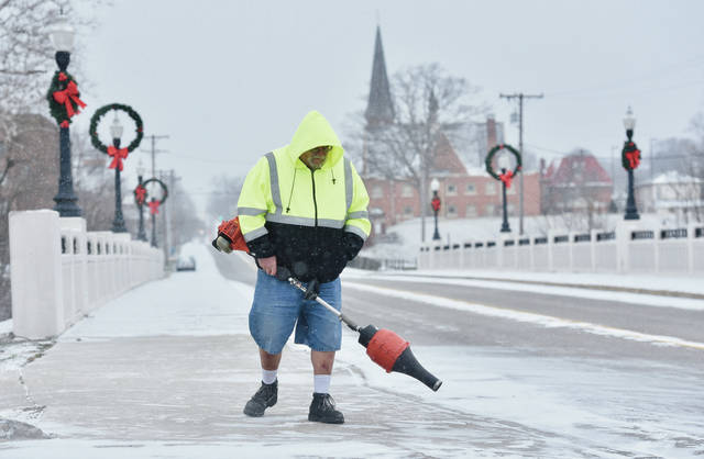"Harry Vonderhuevel, of Sidney, blows snow off of the sidewalk in front of his house next to the North Street Bridge on Christmas day, Friday, Dec. 25. Vonderhuevel said of the snow ""I love it."" Vonderhuevel said he owns H&N Towing and Recovery so the snow is good for business."