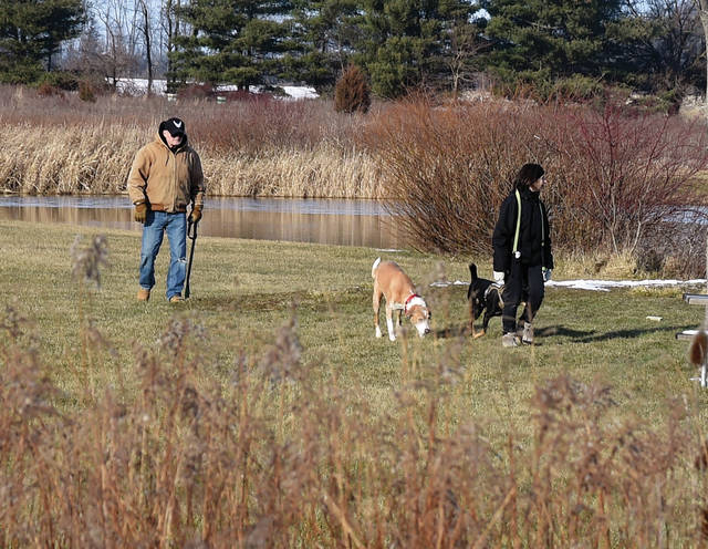 Nick and Janice Grieve of Sidney take advantage of Tuesday sunshine to give their dogs, LG and Rerun some exercise at Garbry Big Woods near Piqua.