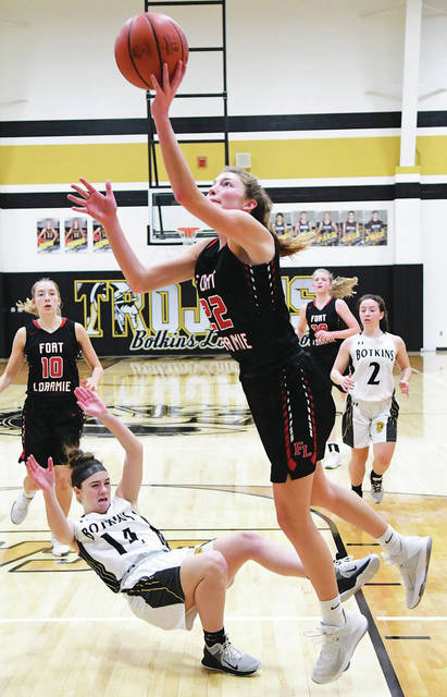 Fort Loramie's Kenzie Hoelscher drives by Botkins' Madison Wendel during a Shelby County Athletic League game on Thursday in Botkins. Hoelscher led the Redskins with 23 points, seven rebounds and five steals.