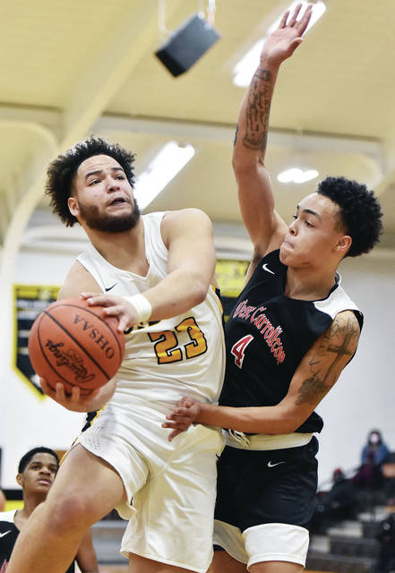 Sidney junior forward Jaden Swiger shoots with pressure from West Carrollton's DeShawn Ferguson during a Miami Valley League game on Wednesday in Sidney. Swiger scored 16 points.
