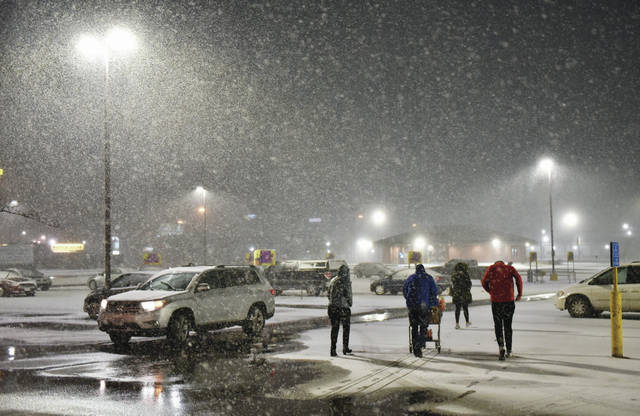 People walk quickly towards their cars in the Kroger parking lot as a heavy snow begins to fall at 10 p.m. on Saturday, Jan. 30.