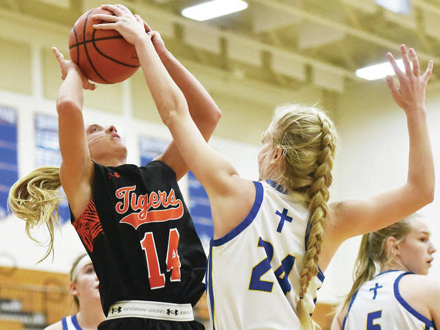 Jackson Center's Ashley Mullenhour shoots as Lehman Catholic's Heidi Toner tries to block during a nonconference game on Tuesday in Sidney. Mullenhour led the Tigers with eight points.