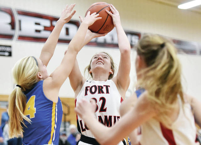 Fort Loramie's Clara Gephart shoots as Russia's Reese Goubeaux tries to block during a Shelby County Athletic League game on Thursday in Fort Loramie. Gephart scored 10 points.