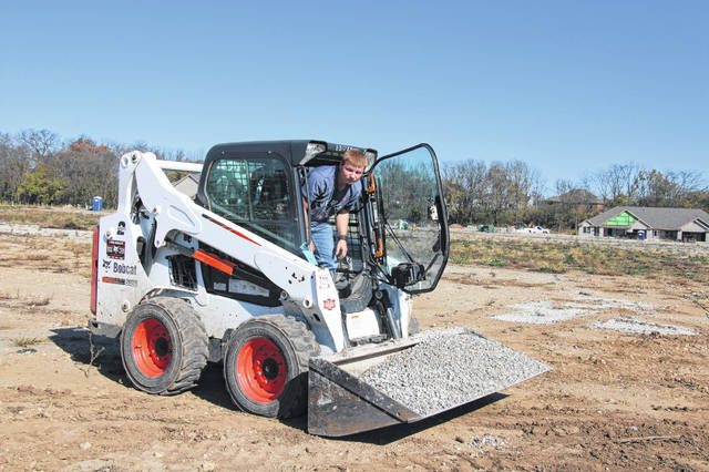 Zach Carter, son of Ryan and Nikki Carter from Houston, works on moving gravel for landscaping.