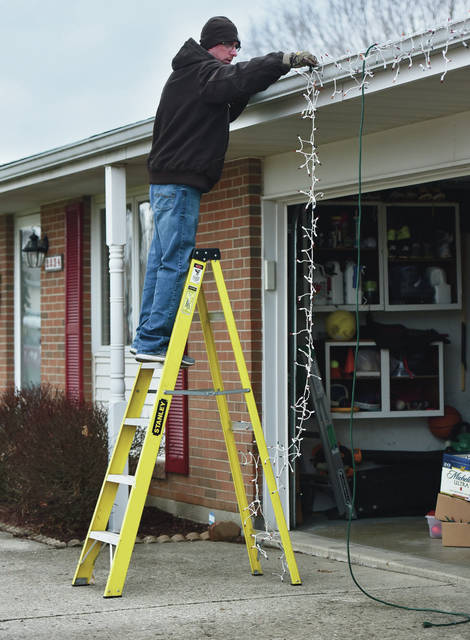 Eric Wooddell, of Sidney, takes down Christmas lights from his house on Sunday, Jan. 4. It took Wooddell about 45 minutes to remove the lights he had placed on the trim of his house and on some bushes. Wooddell said it was much faster taking them down then putting them up.