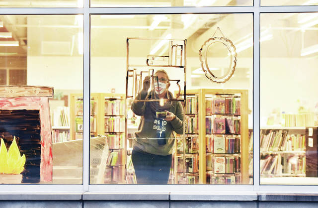 "Amos Memorial Public Library Children's Department Assistant Dawn Rankin, of Piqua, paints a cozy fireplace scene on the library windows on Wednesday, Jan. 7. The scene goes with the libraries' winter reading program theme of ""Snuggle, Sleep, Survive."""