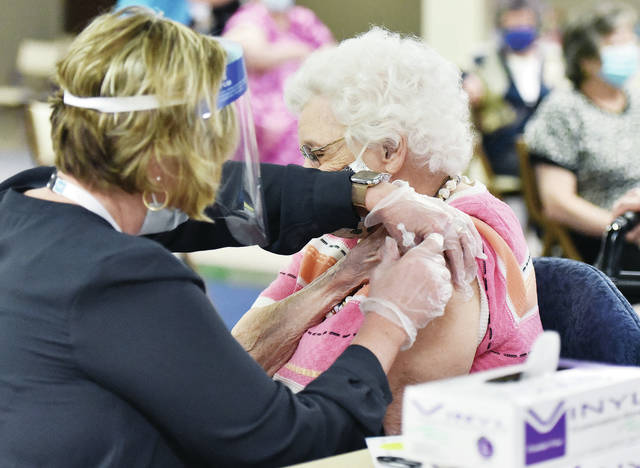 Virginia Fields, a resident of Ohio Living Dorothy Love, is given a COVID-19 vaccination by pharmacist Kara Hellemn, of Lima, at Ohio Living Dorothy Love on Thursday, Jan. 14. Fields was born in 1917, a year before the Spanish flu spread across the world.
