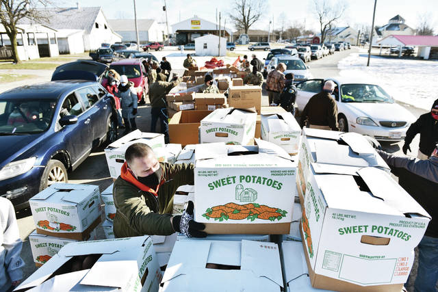 Justin Neu, of Sidney, grabs a box of sweet potatoes to load into a waiting SUV during a food distribution event held by Agape Distribution, West Ohio Food Bank, Shelby County United Way, Ohio National Guard members and other groups at the Shelby County Fairgrounds on Thursday, Jan. 21. Anyone in need was allowed to drive through and stock up on food. Neu is an Alpha Center employee.