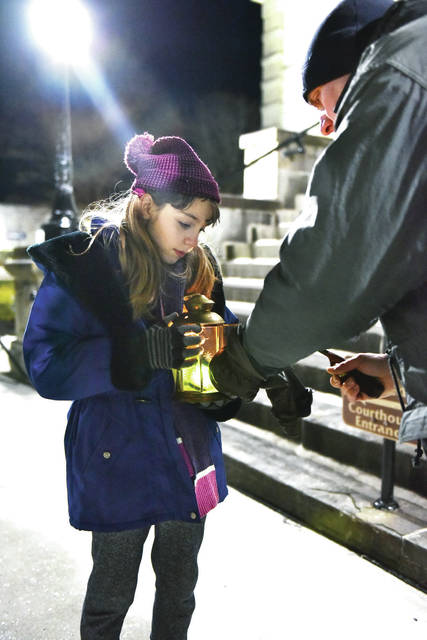 Katharine Schmiesing, 9, has a lamp lit by her father Kevin Schmiesing, both of Sidney, at the Right to Life Candlelight Vigil on the courtsquare on Thursday, Jan. 22. Roughly 100 people took part in walking around the Shelby County Courthouse. Keynote speakers at the vigil were Nathan and Mollie Verdier, both of Sidney, who are founders of Morgan's Place Cemetery in Shelby County. The cemetery will be used for the humane burial of children who die in the womb prior to birth. The Verdiers recently testified in the successful passage of Senate Bill 27 which has been signed by the governor and requires humane burial of babies lost to abortion. Katharine is also the daughter of Anne K. Schmiesing.