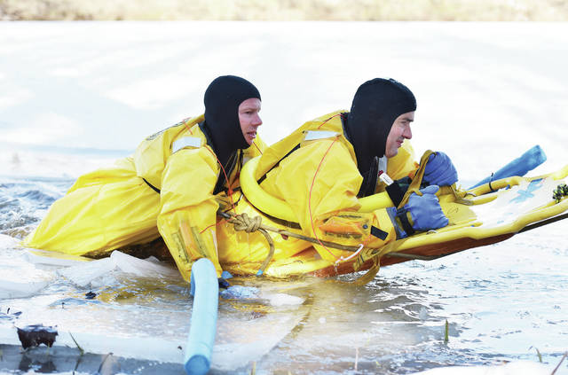 Sidney firefighter Scott Marchal, left, of Minster, practices rescuing Sidney firefighter Wes Goubeaux, of Russia, during an ice training exercise by the Sidney Fire Department in Tawawa Lake on Wednesday, Jan. 20.