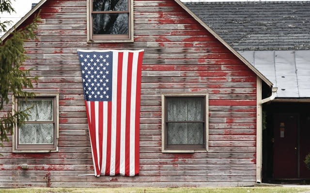 A large U.S. flag adorns the front of an old weather worn barn located along South Main Street in Minster on Sunday, Jan. 24. The barn is owned by Adam and Sara Suchland.