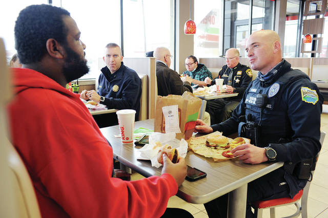 Erick Brooks, left, of Sidney, talks with Sidney Deputy Fire Chief Dallas Davis, back center, and Sidney Police Officer Bryce Stewart, across from Brooks, at Burger King on Tuesday, Jan. 26, during a lunch organized by the Shelby County Board of Developmental Disabilities. In the back booth having lunch are, clockwise, Reserve Sidney Police Officer Mike McRill, Chris Reprogle, of Sidney, Richard Wooddell, of Port Jefferson, and Shelby County Sheriff Jim Frye. Frye said fellow first responders shared what they do with those who showed an interest to become a firefighter or police officer.