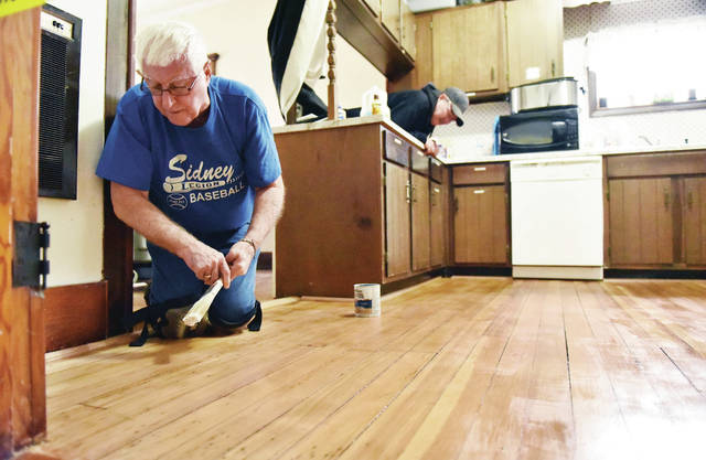 Cecil Steele, left, of Sidney, brushes a layer of clear gloss polyurethane on the wood boards of the upstairs kitchen at Ross Historical Center on Wednesday, Jan. 27, as Richard Bailey, of Minster, peeks over a counter to see how Steele is doing. A first layer of polyurethane was applied to the newly exposed wood on Monday. The volunteers will wait a day and see if the floor needs a third coat. It was decided not to stain the floor to keep the wood its natural color. When the house was first built the the area was the living quarters for housekeepers before being turned into a kitchen. Originally a house the Ross Historical Center has also been used as a funeral home by 3 different companies. The building was built in 1902 and became the Ross Historical Center in 2000.