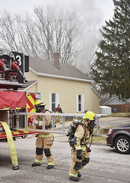 Sidney firefighters remove a ladder from the Quint 3 fire engine while preparing to put out a house fire at 722 Clinton Avenue at around 9:15 a.m. on Wednesday, Jan. 27. Smoke could be seen coming from out the front an back of the top floor of the house. Firefighters used the ladder to reach the top floor window on the front of the house.