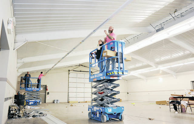 A&E Home Services employees, left to right, Paul Wess, Ronald and Kennedy, both of Sidney, and Stephanie Brewer and Roy Horner, both of Port Jefferson, install new lighting fixtures inside the Beige Building located across from the Secretary's Office at the Shelby County Fairgrounds. Working on Thursday, Jan. 28, they had to finish up the same day in time for people setting-up for the Shelby County Gun & Knife Show that is scheduled for Saturday and will run from 8:30 a.m. - 2 p.m. Besides new lighting ceiling panels have been installed giving the space a more finished look.