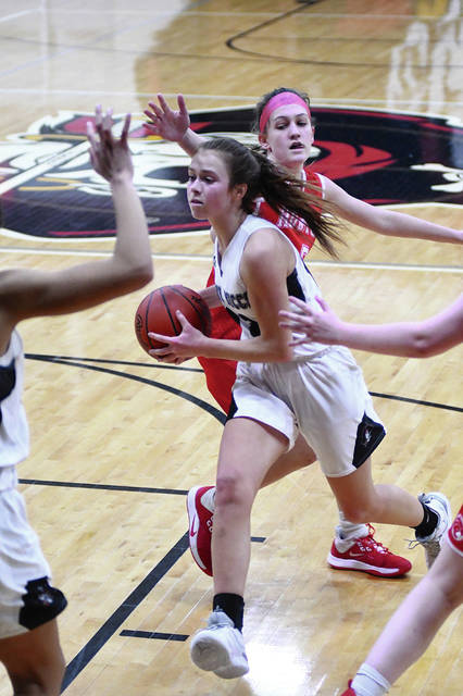 Covington's Gracie Anderson drives to the basket with pressure from Houston's Megan Maier during a nonconference game on Tuesday in Covington.