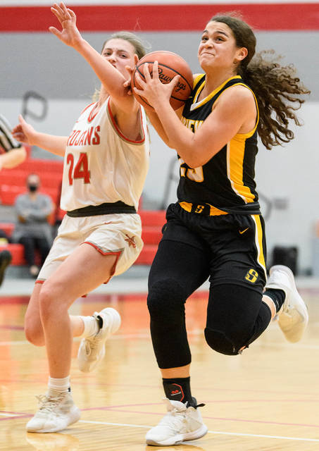 Sidney sophomore guard Allie Stockton drives down the lane with pressure from Troy's Elise McCann during the second half of a Miami Valley League game on Wednesday at the Trojan Activities Center. Stockton led the Yellow Jackets with 16 points.