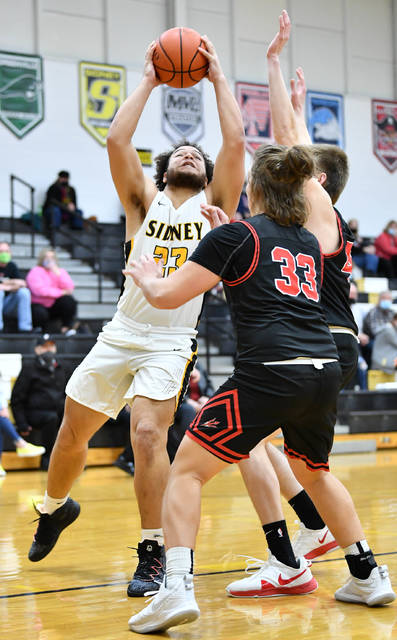 Sidney junior forward Jaden Swiger shoots with pressure from Tippecanoe defenders during the first half of a Miami Valley League game on Saturday in Sidney.