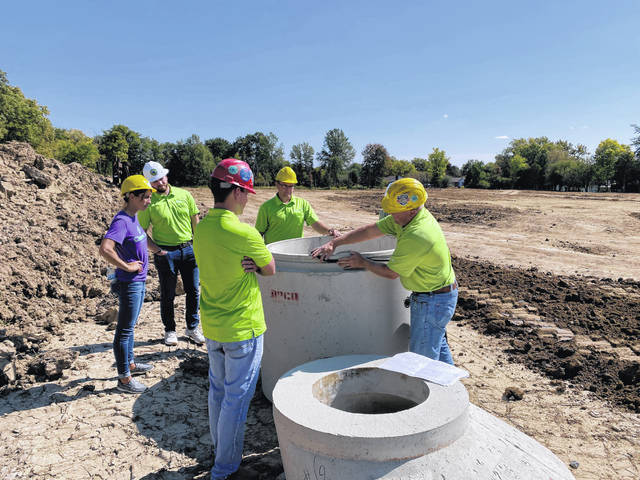 Choice One Engineering employees conduct a site visit at Sidney Crossing residential subdivision on Wapakoneta Avenue.
