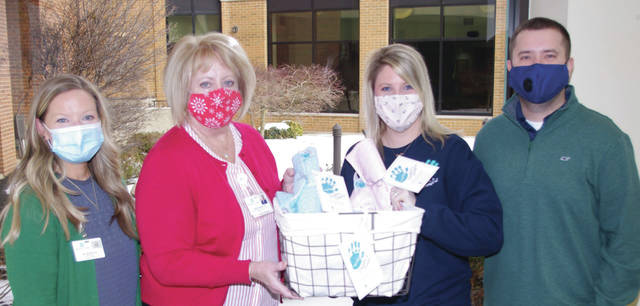 Megan Leidy, far left, and her husband Thomas, far right, present Amy Becker and Linda Haines of Grand Lake Health System with hand-sewn blankets to comfort families of angel babies.