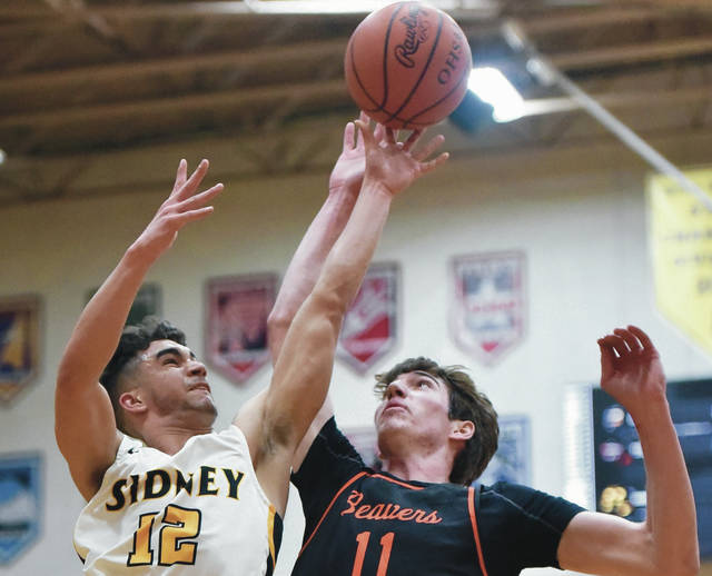 Sidney senior guard Cedric Johnson shoots over Beavercreek's Braden Grant during a Division I sectional semifinal on Saturday at Vandalia-Butler's Student Activity Center. Johnson scored six points and had five assists.