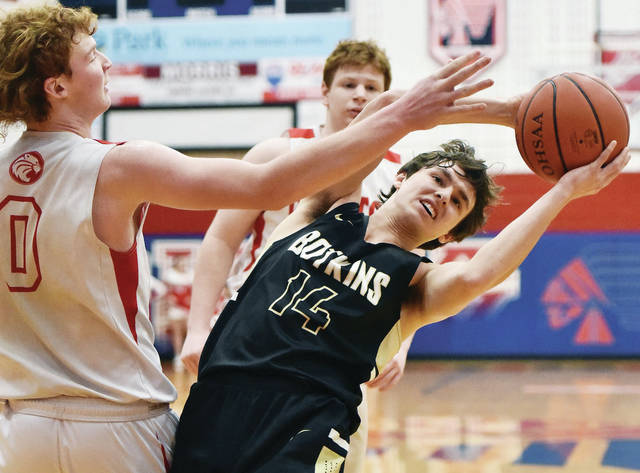 Botkins' Dylan Topp grabs a rebound with pressure from Houston's Jake Leist during a Division IV sectional final on Tuesday at Garbry Gymnasium in Piqua.