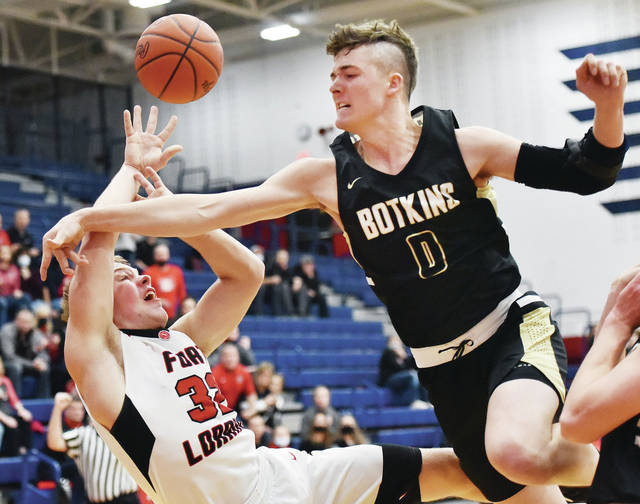 Fort Loramie's Nate Meyer shoots as Botkins' Denton Homan defends during a Division IV district semifinal on Friday at Garbry Gymnasium in Piqua.