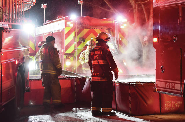 Steam rises from portable water tanks as firefighters fill them for a water source to help fight the house fire on Oak Ridge Drive on Thursday, Feb. 11.