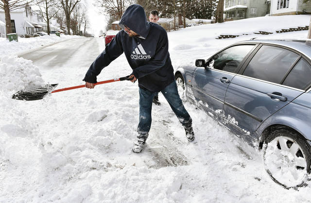 Jason Kessler, of Sidney, shovels snow from around a car that had been blocked in by snow from snowplows along North Ohio Avenue on Tuesday, Feb. 16.