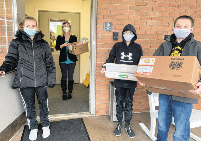 Versailles FFA members are seen at the Versailles Health Care Center on Jan. 25 with Versailles Health Care Center staff. Versailles FFA members that assisted Emma Middendorf, left rto right, Grifon Miller and Jeremiah Wagner. They dropped off craft bags and snacks for staff and residents.