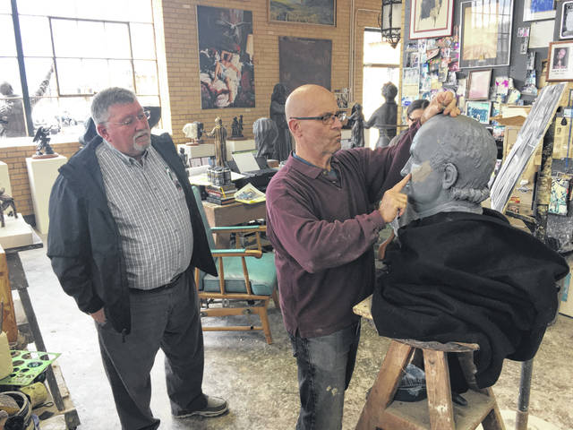 "Sculptor Alan Cottrill adds ""flesh"" to the face of his clay model of General Isaac Shelby following the suggestion of Bicentennial Co-Chair Bob Guillozet during the visit to the sculptor's Zanesville studio on March 20."