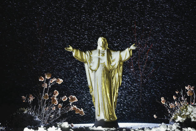 Snow flies horizontally past a Jesus statue partially covered in snow next to Lehman Catholic High School on Thursday, Feb. 4. Snow made for poor driving conditions in the late afternoon.
