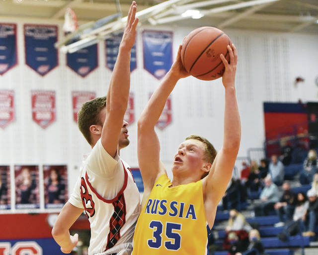 Russia's Xavier Phlipot looks to shoot over Newton's Harold Oburn at Piqua on Saturday.