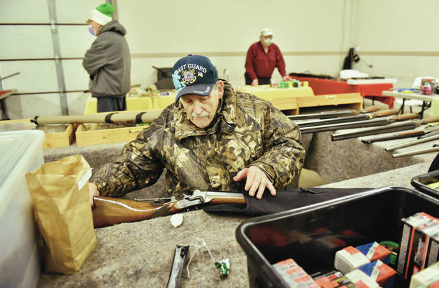 Ace Bachman, of Houston, puts away an 1879 Remington Hepburn rifle at his booth while selling at the Shelby County Gun and Knife Show in the Beige Building at the Shelby County Fairgrounds on Saturday, Jan. 30. Bachman said he has been collecting guns since he was 9-years-old. He is now 82-years-old. At the age of 9 Bachman was swimming at the Minster swimming pool when a man asked him if he would be willing to mow his lawn for the summer. Bachman told the man he would talk about it after he finished swimming. When finished the man took Bachman to his she. Bachman didn't see a lawnmower anywhere. The man told him to look up and Bachman saw a manual hand push lawnmower hanging from chains. The man said he would give Bachman a 20 gage bolt action shot gun at the end of the summer as payment. After a long summer slow hard work Bachman earned his first gun.