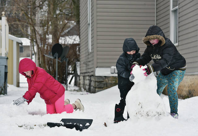 Abigail Danner, left to right, 9, rolls a new snowman head as her brother Cash Danner, 5, tries to help their neighbor Riley Ramirez, 8, all of Sidney, to keep the top of their snowman from continuing to disintegrate along Main Avenue on Sunday, Jan. 31. Abigail and Cash are the children of Josh Danner and Brianna Johnson. Riley is the daughter of Sarah and Andy Ramirez.