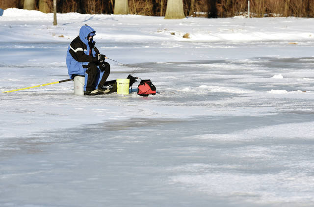 Ray McMaster, of New Bremen, ice fishes on Lake Loramie on Tuesday, Feb. 2. McMaster was using a Vexilar sonar detector to know how close fish were to his bait. Three bluegills worth keeping sat in McMasters bucket. McMaster was fishing on 5 inches of ice but not too far away parts of the lake still had open water.