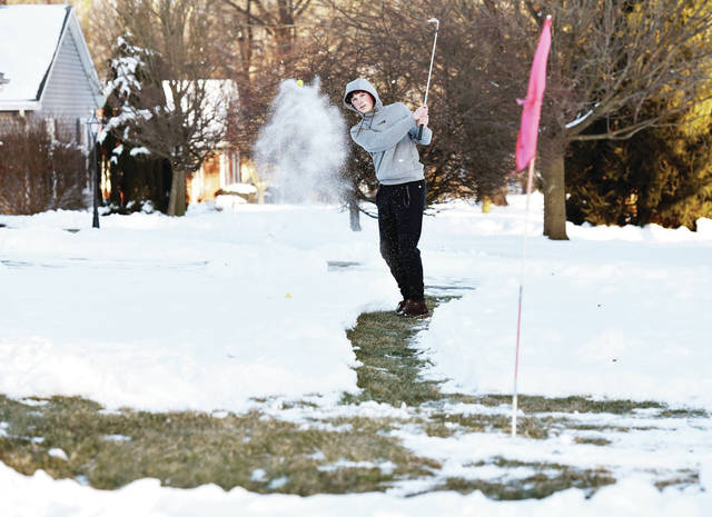 Sidney Jr and Varsity golfer Kaden Abbott, 17, of Sidney, son of Angie Abbott and Ric Abbott, practices his chipping on a green, complete with hole and flag, that he created in his front yard on Pinehurst Street by shoveling snow down to the grass to create a path and a circle. Abbott also shoveled squares on the other side of his driveway for longer chip shots. Abbott was practicing on Wednesday, Feb. 3 after school.