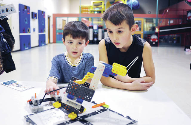Niles Legge, left, 5, operates a robotic crane as his brother Nolan Legge, 7, both of Anna, watches during an open house for the Level-Up STEM and Robotics Club at the Sidney-Shelby County YMCA on Thursday, Feb. 4. The club will be run by three certified instructors who will teach members lessons in engineering, physical science, simple machines and coding. The club will meet at the YMCA twice a month. The club is for kindergarten to sixth graders. People interested can contact the Sidney-Shelby County YMCA. The program was made possible with a grant from The Monarch Machine Tool Company. Niles and Nolan are the children of Shane and Kirstyn Legge.