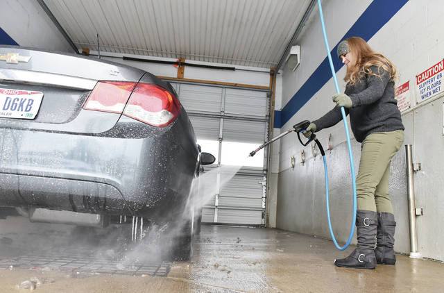 Gara Ralston, of Sidney, cleans off grime, including a few icicles, from a Superior Auto car at The Auto Spa on Tuesday, Feb. 9. The self-serve car wash had a steady flow of vehicles coming through with people wanting to clean off winter grime. Salt, laid down on slick winter roads, is very corrosive to vehicles.