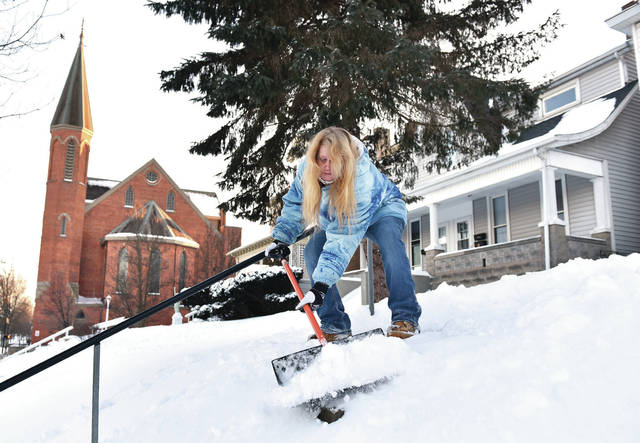 Dawn Auville, of Sidney, shovels the steps in front of her house on South Main Avenue on Tuesday, Feb. 16. People continue to dig themselves out of the snow that fell from Monday into Tuesday.