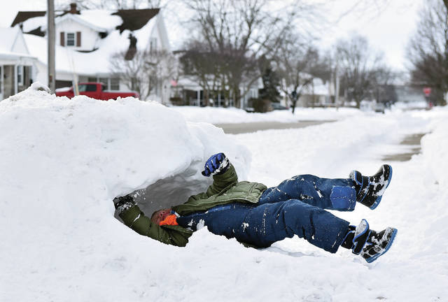 Oliver Eilerman, 6, of Minster, son of Dave and Jessica Eilerman, digs a hole into a pile of snow next to his family's driveway on Third Street to make a snow fort on Wednesday, Feb. 17.