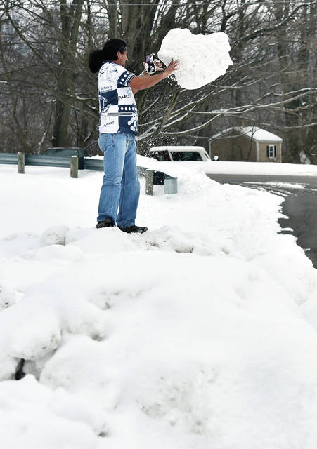 Luis Callejas, of Sidney, uses a cell phone video call to show a friend in Mexico a chunk of snow he picked up from the piles of snow at the Custenborder Field parking lot on Thursday, Feb. 18. Callejas has been making the most of the snow by constructing snowmen, digging a snow fort, burying people in snow and taking lots of pictures of the snow.