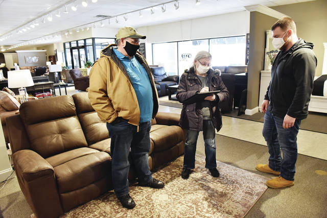 Dale and Janice Wick, left to right, of Plattsville, fill out some paperwork for Goffena Furniture Manager Drew Goffena after the Wicks won a new couch in the Sidney Daily News and Local Businesses Valentine's Day Giveaway on Friday, Feb. 19.