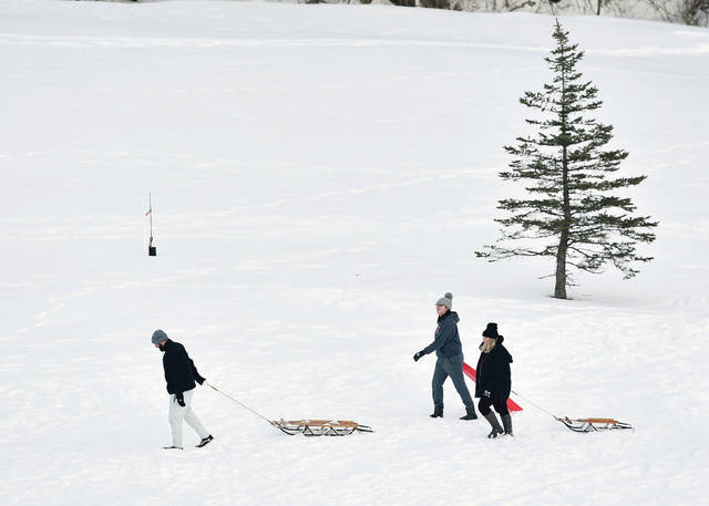 Calling it a day after sledding at the Moose Golf Course on Monday, Feb. 22 are, left to right, Ben Davis, Alexa Rivera, 17, daughter of Cindy and Mario Rivera, and Jasmine Cox, all of Sidney. While a lot of snow had melted there was still plenty left for sledding though warming temperatures may change that soon.
