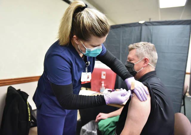 Anna Local Schools Superintendent Andy Bixler is given a COVID-19 vaccine shot by RN Sherry Dearth, of Sidney, at Wilson Health on Friday, Feb. 26.