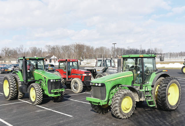 Fort Loramie FFA members prepare to leave the Fort Loramie High School parking lot in the tractors they drove to school on Thursday, Feb. 25. The students drove their tractors to and from school as part of FFA week.