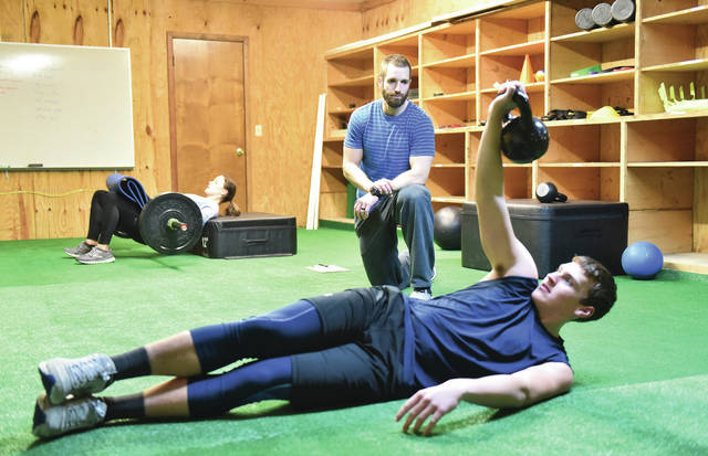 Eric May, kneeling, of Anna, oversees the conditioning of Emma Koenig, left, 17, of Botkins, daughter of Heide and Aaron Koenig, and Drew Dammeyer, of St. Marys, inside his new physical therapy and sports performance business in Botkins on Wednesday, Dec. 16.